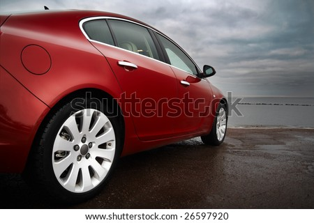 Rear-side view of a luxury cherry red car with dramatic sky - stock photo