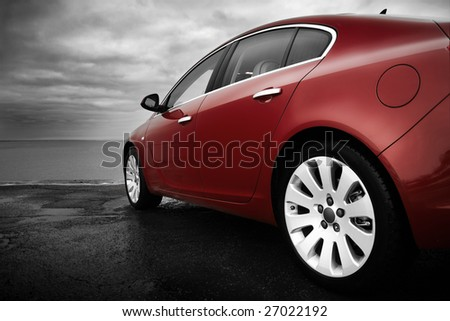 Rear-side view of a luxury cherry red car with monochrome background - stock photo