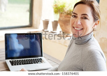 Rear side view of a smart professional woman using her laptop computer while sitting near a large glass window at home overlooking the garden turning to camera and smiling. - stock photo