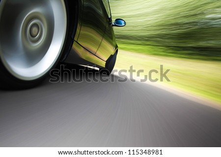 rear side view of a sport car in blurred motion - stock photo