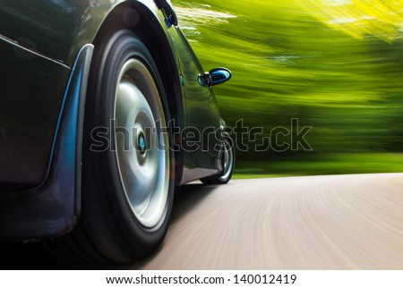 Rear side view of black car in turn. - stock photo