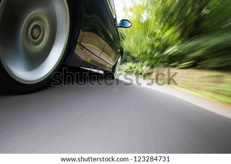 Rear side view of black family car driving fast on forest road - stock photo