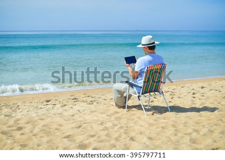 Rear side view om man using digital tablet relaxing on chair at the ocean beach outside. Blue sky outdoors background