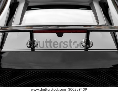 Rear spoiler. Part of black sports car. - stock photo