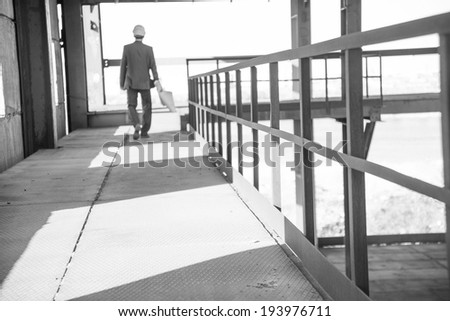 Rear view An architect full length walking on metal floor inside building with blueprints paper plan . Steel frame construction. Focus on rusty fence in perspective - stock photo