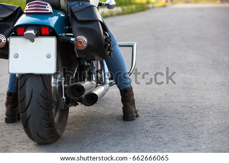 Rear view at the chrome of chopper motorbike with female legs in boots standing on asphalt road, copy space
