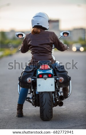 Rear view at the female motorcyclist sitting on the classic chopper motorbike