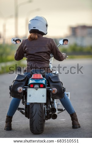 Rear view at the woman motorcyclist sitting on the classic chopper motorbike on urban asphalt road