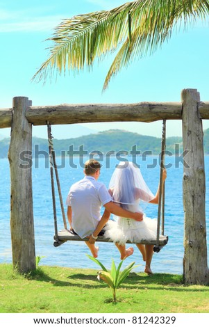 Rear view bride and groom on the swing - stock photo
