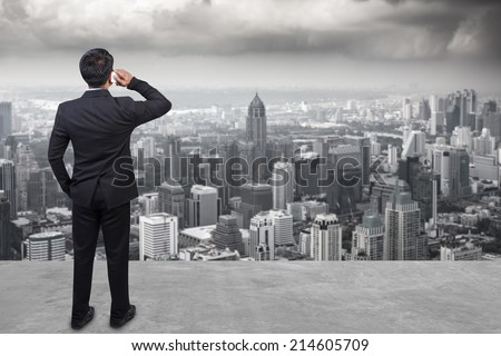 rear view business man in suit speaking by the phone against urban scene balcony over looking city dusky before rain falling