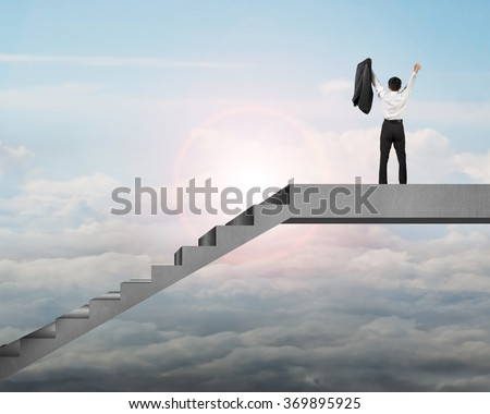 Rear View businessman cheering on top of concrete stairs with cloudy sky and sunlight - stock photo
