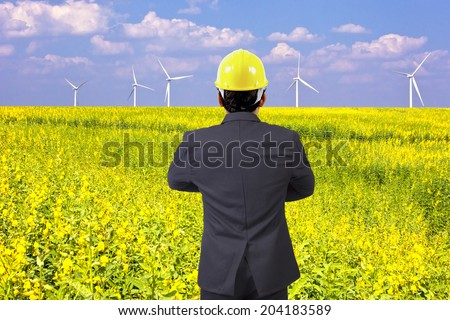 rear view businessman standing at wind turbines in a flower field, eco power concept - stock photo