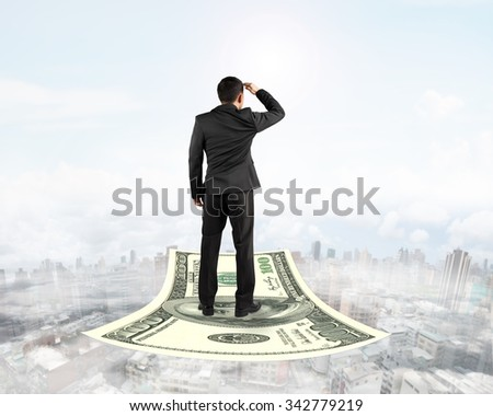 Rear view businessman standing on money flying carpet and watching the front, with fog sky cityscape background. - stock photo