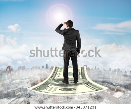Rear view businessman standing on money flying carpet and watching the front, with sunny sky cityscape background. - stock photo