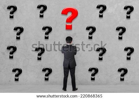 rear view businessman with his arms crossed confused thinking something looking at many question marks on concrete wall - stock photo