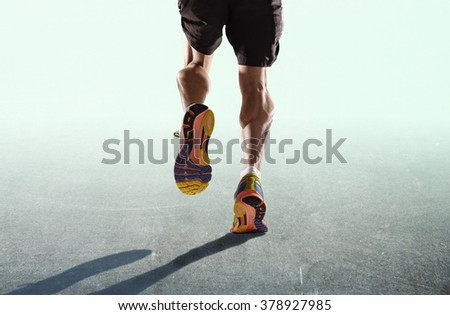 rear view close up strong athletic legs and running shoes of sport man jogging isolated in fitness healthy lifestyle high performance and endurance concept in advertising style lighting  - stock photo