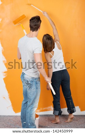 Rear view couple holding their paint rollers up and looking at the partially painted wall - stock photo