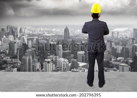 rear view engineer builder in protective safety equipment hard hat and against balcony overlooking city dusky before rain falling - stock photo