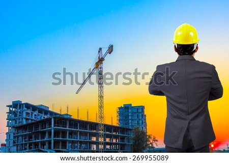 rear view engineer standing cross one's arm chest working at building construction site against beautiful sky sunset