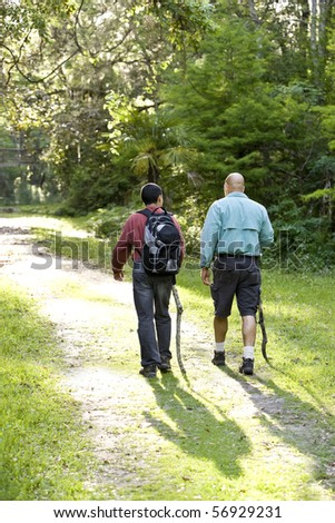 Rear view father and teenage son hiking on path in woods - stock photo