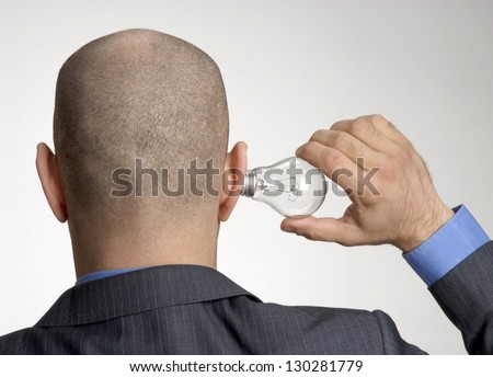 Rear view from a bald head man holding a light bulb on his ear.