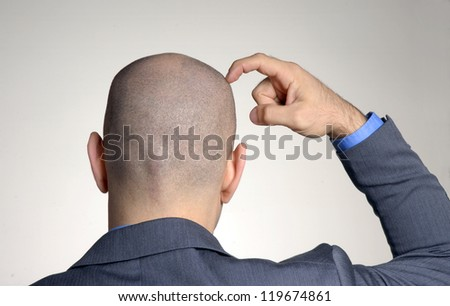 Rear view from a bald head man,thinking and touching his head. - stock photo