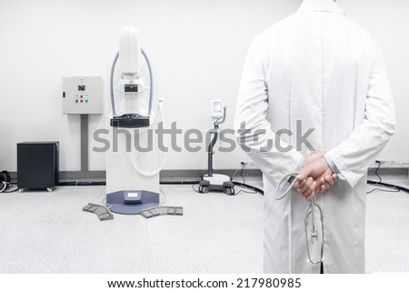 rear view image of doctors with stethoscope pose arms crossed behind back looking at mammography breast screening modern device in hospital laboratory  - stock photo
