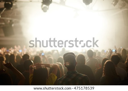 Rear view image of large crowd in front stage in bright light, watching music performance and dancing, focus on young couple in foreground