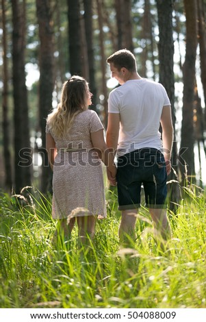 Rear view image of young couple expecting baby standing on the meadow at forest
