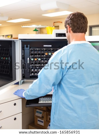 Rear view male lab technician loading samples in hematology analyzer