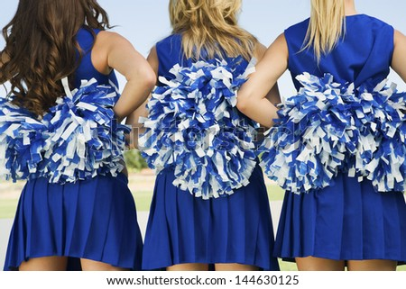 Rear view midsection of three cheerleaders holding pom poms - stock photo