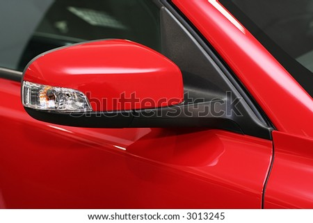 rear-view mirror by the red sports machine - stock photo
