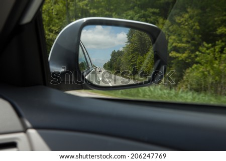 Rear view mirror, highway traffic visible.