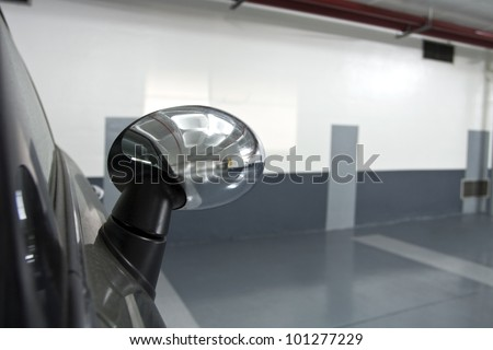 Rear view mirror of a parked car/parked car - stock photo