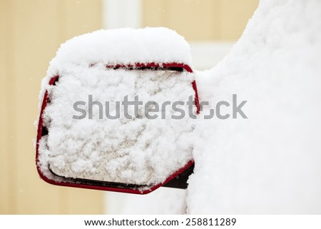 Rear view mirror of a truck covered in snow during a storm - stock photo