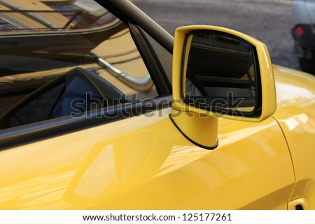 rear view mirror of yellow car