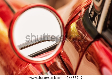 Rear-view mirror on red veteran car. Vintage car. Old automobile. Vibrant colors. - stock photo