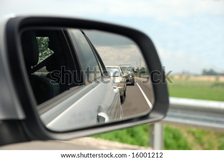 Rear view mirror reflecting a line of cars behind - stock photo