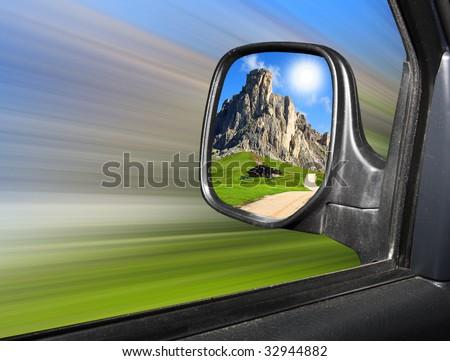 Rear view mirror reflecting beautiful mountain scenery - stock photo