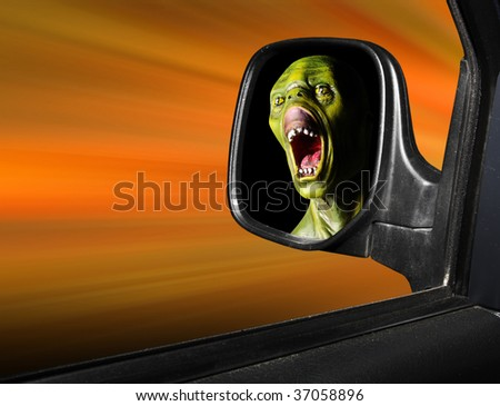 Rear view mirror reflecting fearful monster face - road safety metaphor - green wooden head is unauthorized homemade work. - stock photo