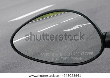 Rear view mirror with warning text objects in mirror are closer than they appear, reflecting road, left side lateral, macro closeup, tarmac asphalt background reflection, white lines, arrows marking - stock photo