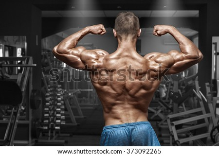 Rear view muscular man posing in gym, showing back and biceps. Strong male naked torso, working out - stock photo