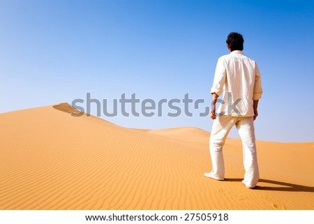 Rear view of a adult white man standing on a sand dune in the desert. Erg Chebbi, Maroc