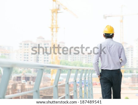 Rear view of a Asian Indian male contractor engineer with hard hat standing in front construction site, inspecting the progress. - stock photo