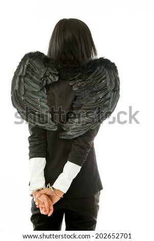 Rear view of a Asian young businesswoman dressed up as black angel handcuffs isolated on white background - stock photo