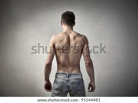 Rear view of a bare-chested muscular young man - stock photo