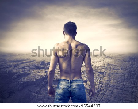 Rear view of a bare-chested muscular young man with dried up landscape - stock photo