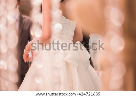 Rear view of a beautiful bride in a white wedding dress standing in a wedding. - stock photo