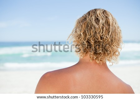 Rear view of a blonde man standing in front of the ocean - stock photo