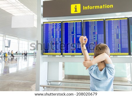 Rear view of a bored kid crossing his arms and looking panel flight times in the airport - stock photo